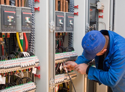 A service employee working on a big panel